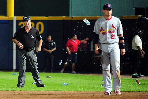 An umpire reacts after bottles and cups are thrown on the field by fans after the home fans disagree with an infield fly ruling on a ball hit by Andrelton Simmons #19 of the Atlanta Braves in the eighth inning while taking on the St. Louis Cardinals during the National League Wild Card playoff game at Turner Field on October 5, 2012 in Atlanta, Georgia
