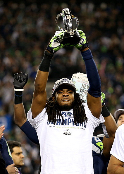Cornerback Richard Sherman #25 of the Seattle Seahawks celebrates with the George Halas Trophy
