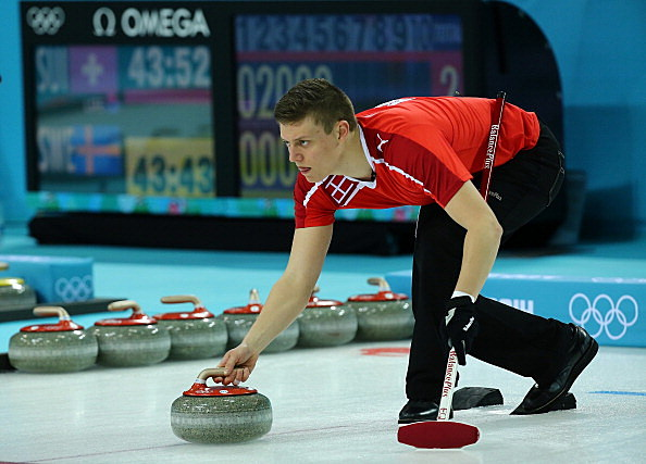 Troels Harry of Denmark releases a stone during the Men's Curling Round Robin match between Russia and Great Britain on day 3 of the Sochi 2014 Winter Olympics