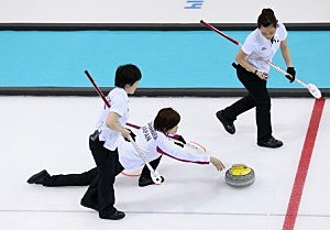 Ayumi Ogasawara of Japan delivers the stone as Michiko Tomabechi and Yumie Funayama prepare to sweep the ice during the Curling Women's Round Robin match between Japan and Republic of Korea during day four of the Sochi 2014 Winter Olympics