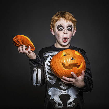 red hair kid in Halloween costume holding a orange pumpkin